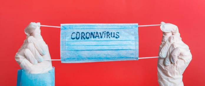 mani con guanti che tengono una mascherina chirurgica con la scritta coronavirus