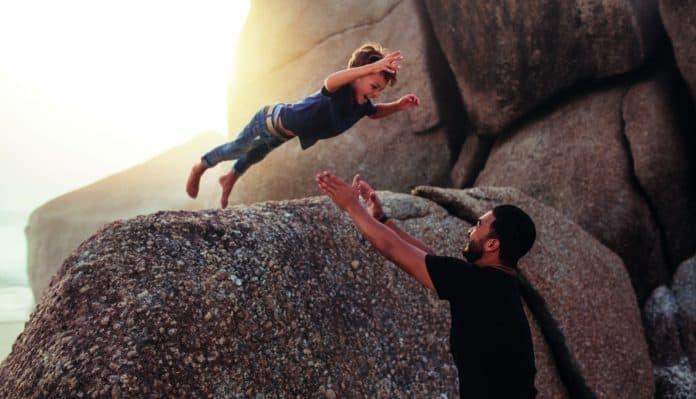 bambino che si lancia da una scogliera verso le braccia del papà