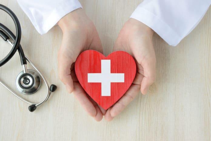 mani di un dottore con camice che stringono un cuore rosso di legno con disegnata sopra una croce bianca, stetoscopio