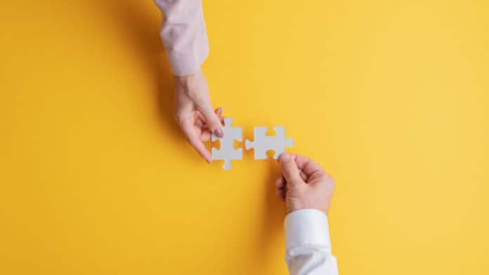 due mani che incastrano tra loro due pezzi di puzzle
